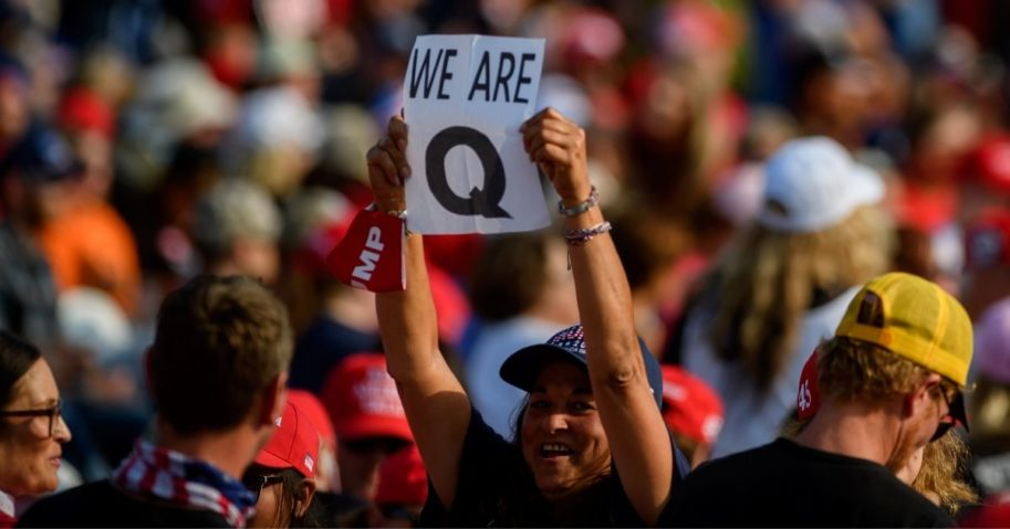 A woman holds up a QAnon sign to the media as attendees wait for President Donald Trump to speak at a campaign rally at Atlantic Aviation on Sept. 22, 2020, in Moon Township, Pennsylvania.