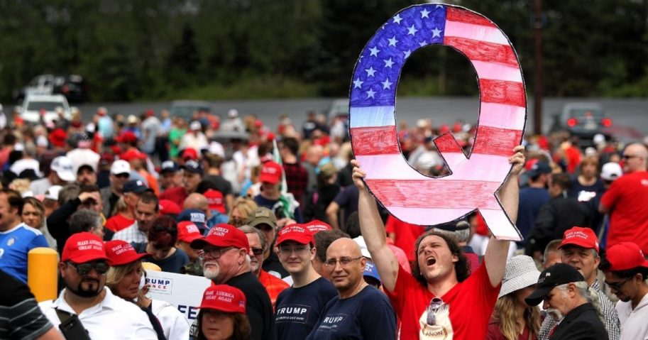 "A man holds up a large ""Q"" sign while waiting in line to see President Donald Trump at his rally on Aug. 2, 2018, at the Mohegan Sun Arena at Casey Plaza in Wilkes Barre, Pennsylvania."