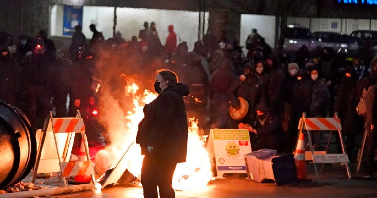 A protester walks past burning trash during a protest against police brutality, late Sunday in downtown Tacoma, Washington.
