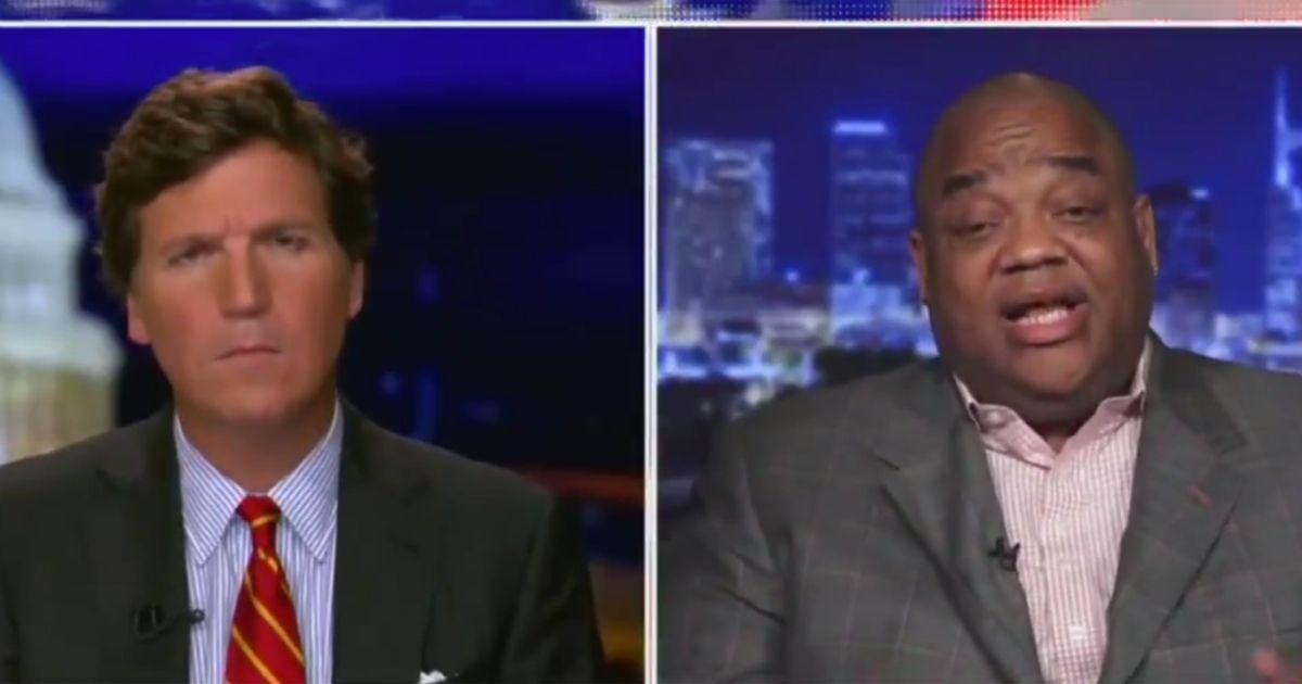 "Fox News host Tucker Carlson, left, interviews sports journalist Jason Whitlock on ""Tucker Carlson Tonight"" on Wednesday."