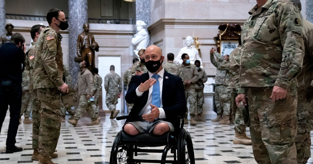 U.S. Rep. Brian Mast, the Florida Republican who lost his legs in an IED attack while serving in Afghanistan in 2010, gives members of the National Guard a tour of the Capitol on Wednesday.