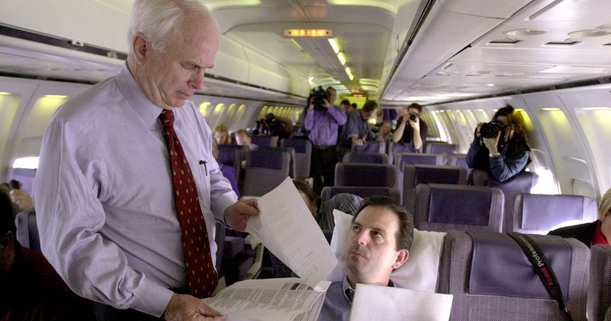 Former Republican presidential hopeful John McCain looks over documents with campaign adviser John Weaver while flying from Virginia Beach to Bismarck, North Dakota, on Feb. 28, 2000.
