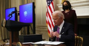 President Joe Biden signs executive orders as Vice President Kamala Harris looks on in the State Dining Room of the White House on Thursday.
