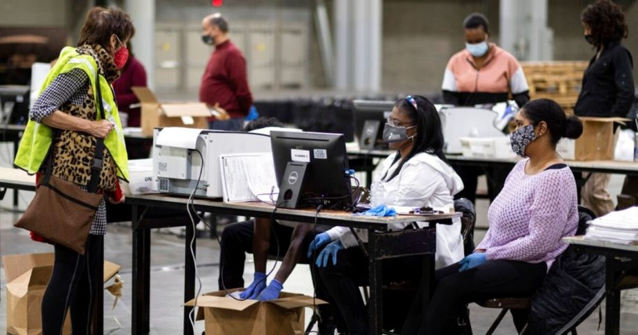 A GOP observer, left, watches as workers scan ballots as the Fulton County presidential recount gets under way Nov. 25, 2020, at the Georgia World Congress Center in Atlanta.