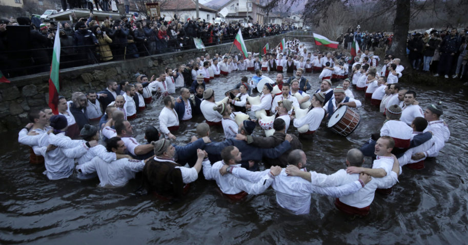 Citizens of the mountain town of Kalofer in central Bulgaria, clad in traditional garments, stand in the icy Tundzha River in an old ritual marking the feast of Epiphany on Jan. 6, 2021.