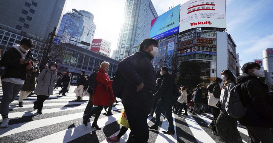 People walk along pedestrian crossings on Jan. 25, 2021, in Tokyo.