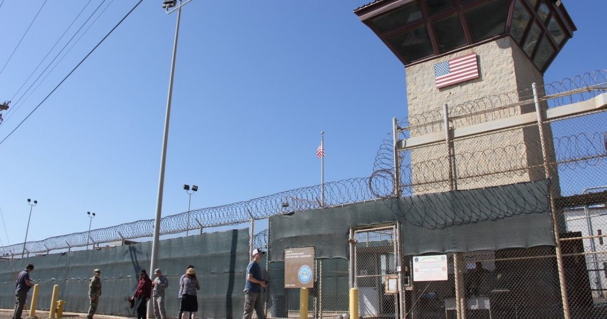 People walk past a guard tower outside the fencing of Camp 5 at the US Military's Prison in Guantanamo Bay, Cuba on Jan. 26, 2017.