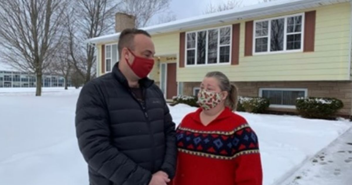 Bryan and Kim Burt in front of their house on Canada's Prince Edward Island that has been used as bait in a rent scam.