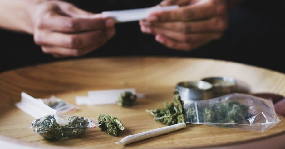 A man rolls a joint of marijuana in this stock image.