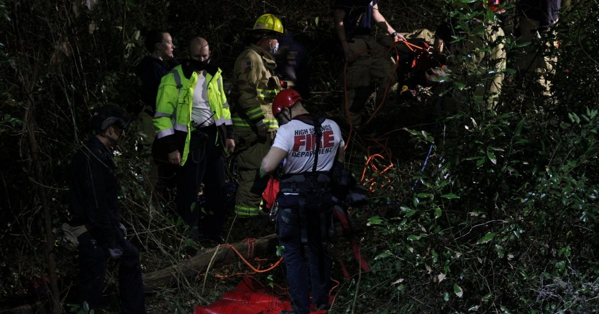 Rescuers stand near the 40-foot sinkhole that a car drove into. One of the two people in it was able to climb out of the sinkhole but the other one had to be rescued.