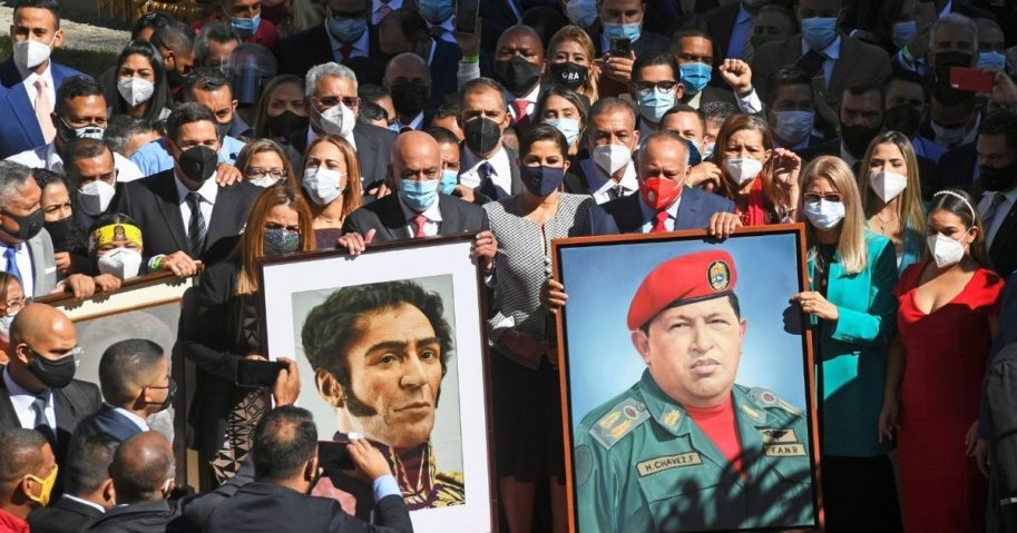 Venezuelan pro-government deputies arrive to the National Assembly building carrying portraits of Simon Bolivar, left, and the late president Hugo Chavez in Caracas on Jan. 5, 2021.