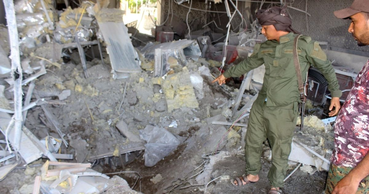Fighters with a Saudi-backed coalition assess the damage inside the airport of Yemen's southern city of Aden on Dec. 31, 2020, a day after explosions rocked the building, killing or injuring dozens of people.