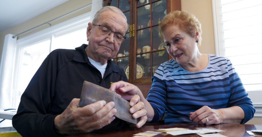 Paul Grisham and his wife Carole Salazar look over his wallet and the items that were inside when he lost it in Antarctica back in 1968 at their home in San Diego, California, on Feb. 3, 2021.