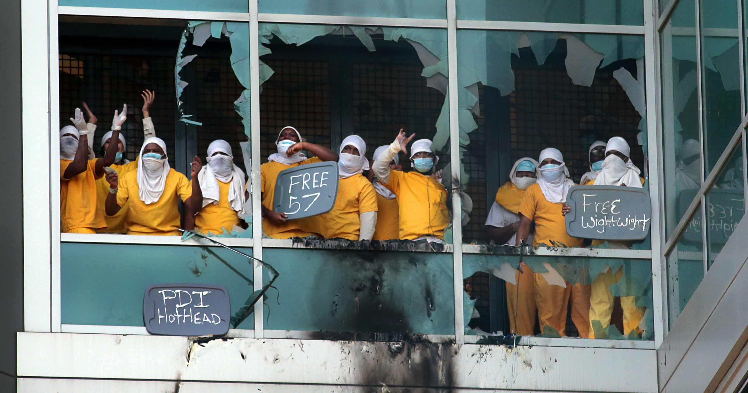 Inmates stand at broken windows at the St. Louis Justice Center on Feb. 6, 2021, in St. Louis, Missouri.