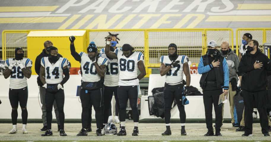 Carolina Panthers players stand for the national anthem before a game against the Green Bay Packers at Lambeau Field on Dec. 19, 2020.