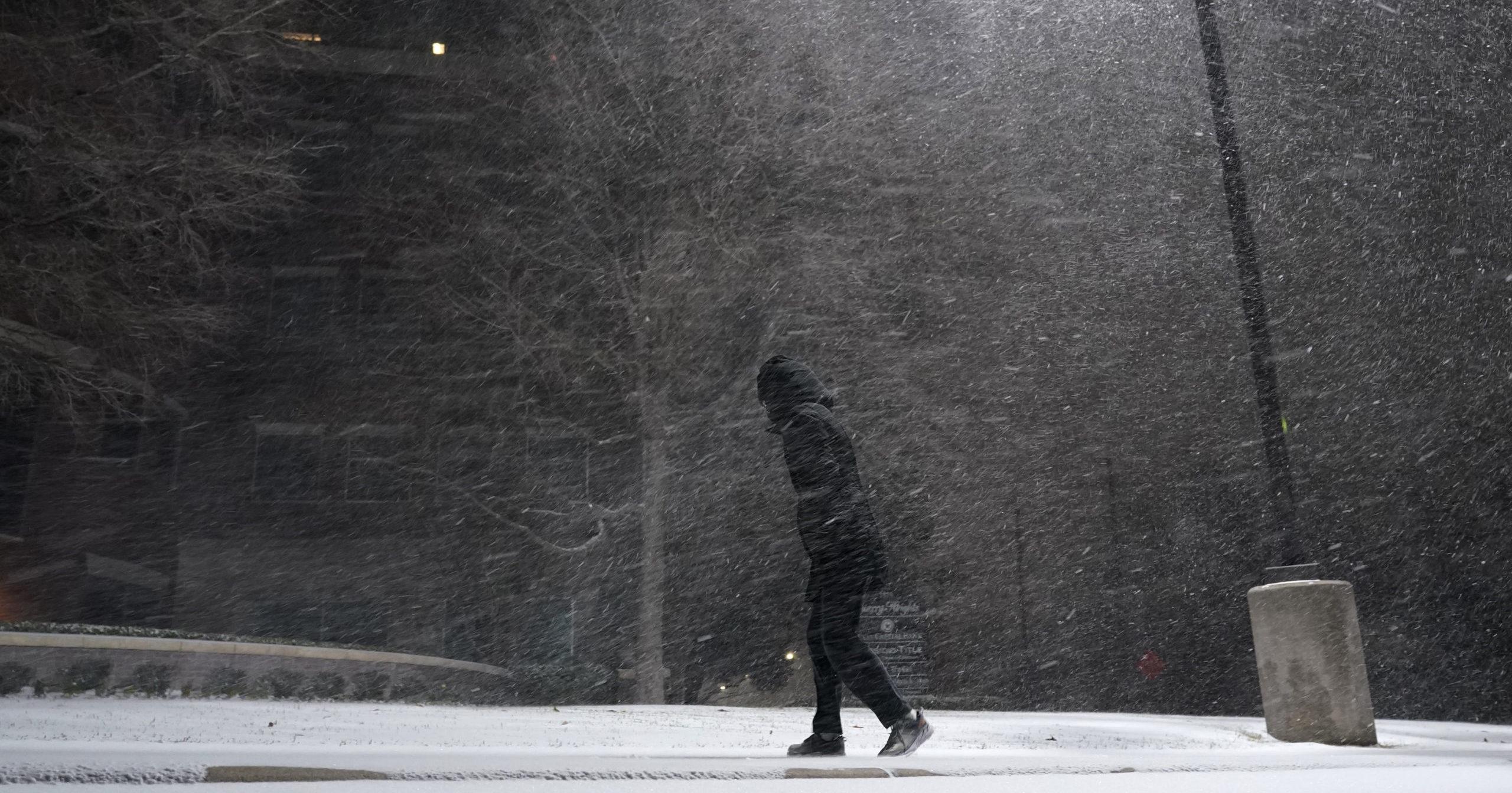 A woman walks through falling snow in San Antonio on Sunday.
