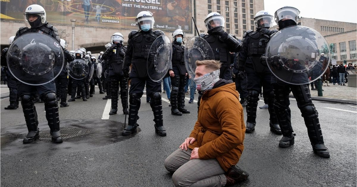 A man kneels in front of police as people take part in a protest against government-imposed measures to tackle the coronavirus pandemic on Sunday in Brussels, Belgium.