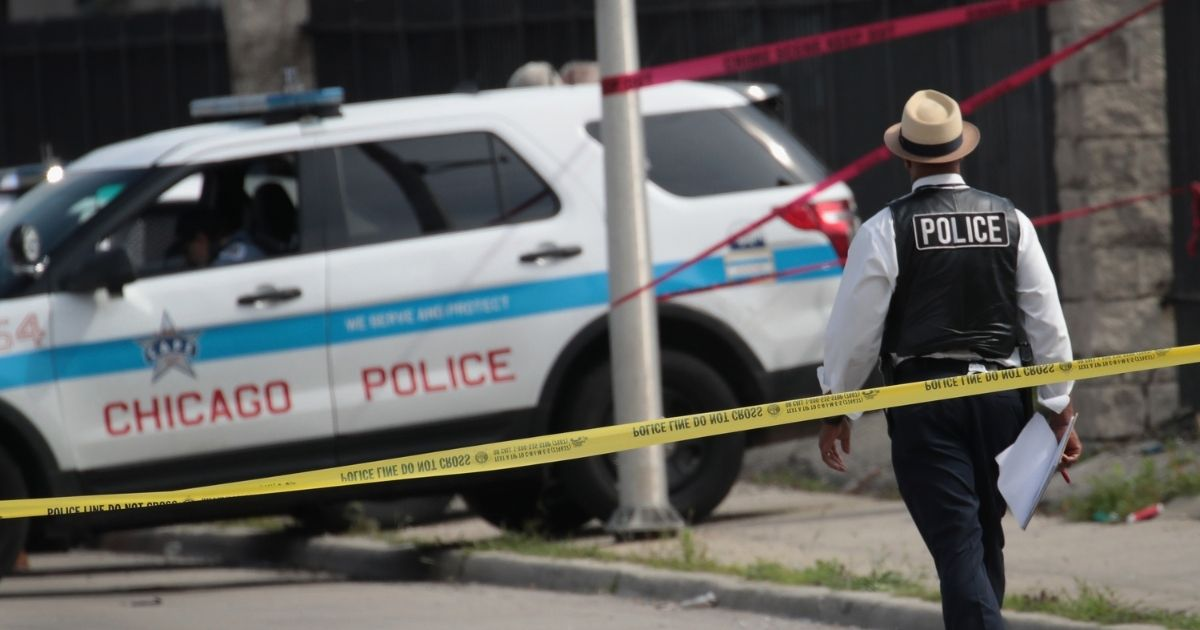 Police investigate the murder of a young man found shot to death in the back seat of a bullet-riddled car on June 30, 2017, in Chicago.