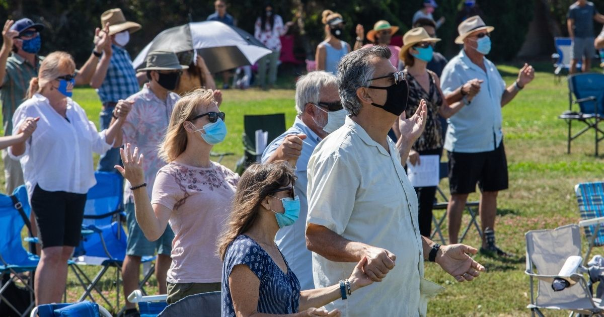 People wearing facemaks attend an outdoor Sunday service at Saints Simon & Jude Catholic Church in Huntington Beach, California, on July 19, 2020.