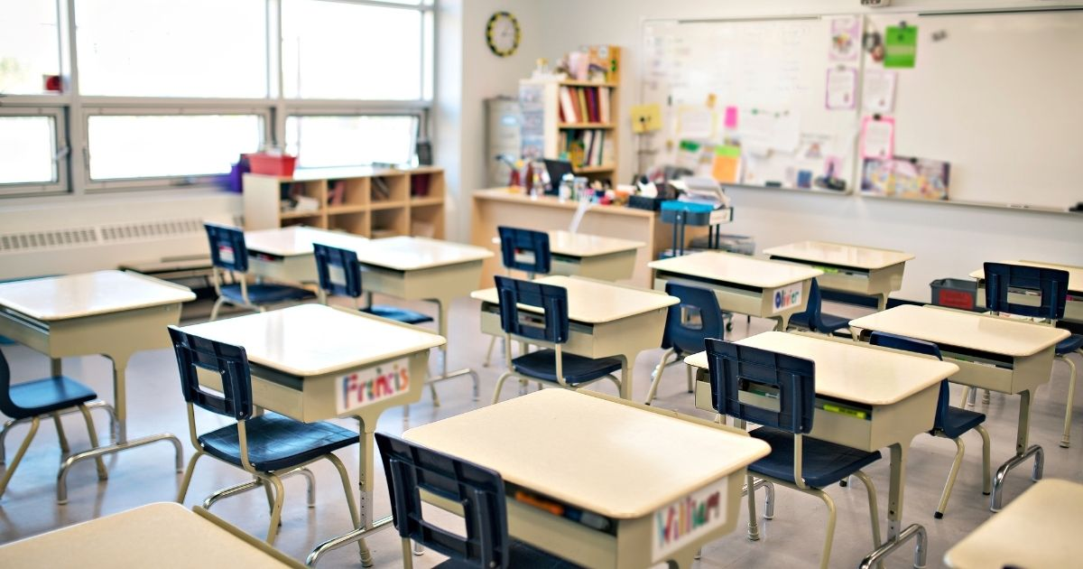 An empty classroom is pictured in the stock image above.