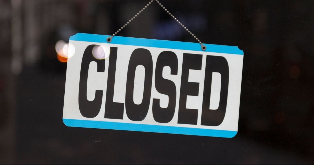 """A """"closed"""" sign in a shop window is pictured in the stock image above."""