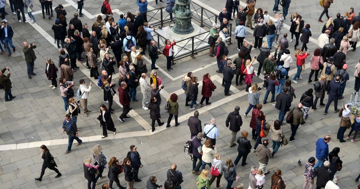 """This stock photo shows a large crowd of people taking photos on a city street. Recent data has shown four states in the U.S. appear to have reached """"herd immunity"""" from the coronavirus."""