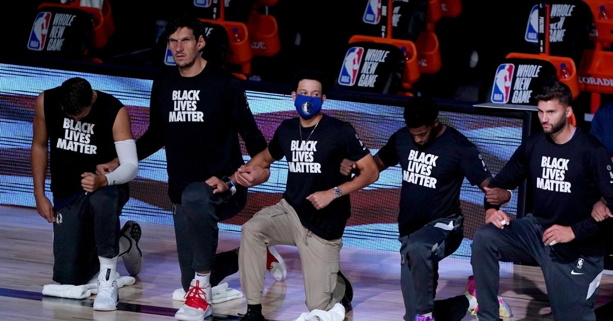 Dallas Mavericks players kneel in honor of the Black Lives Matter movement during the playing of the national anthem prior to an NBA basketball game against the Los Angeles Clippers on Aug. 6, 2020, in Lake Buena Vista, Florida.