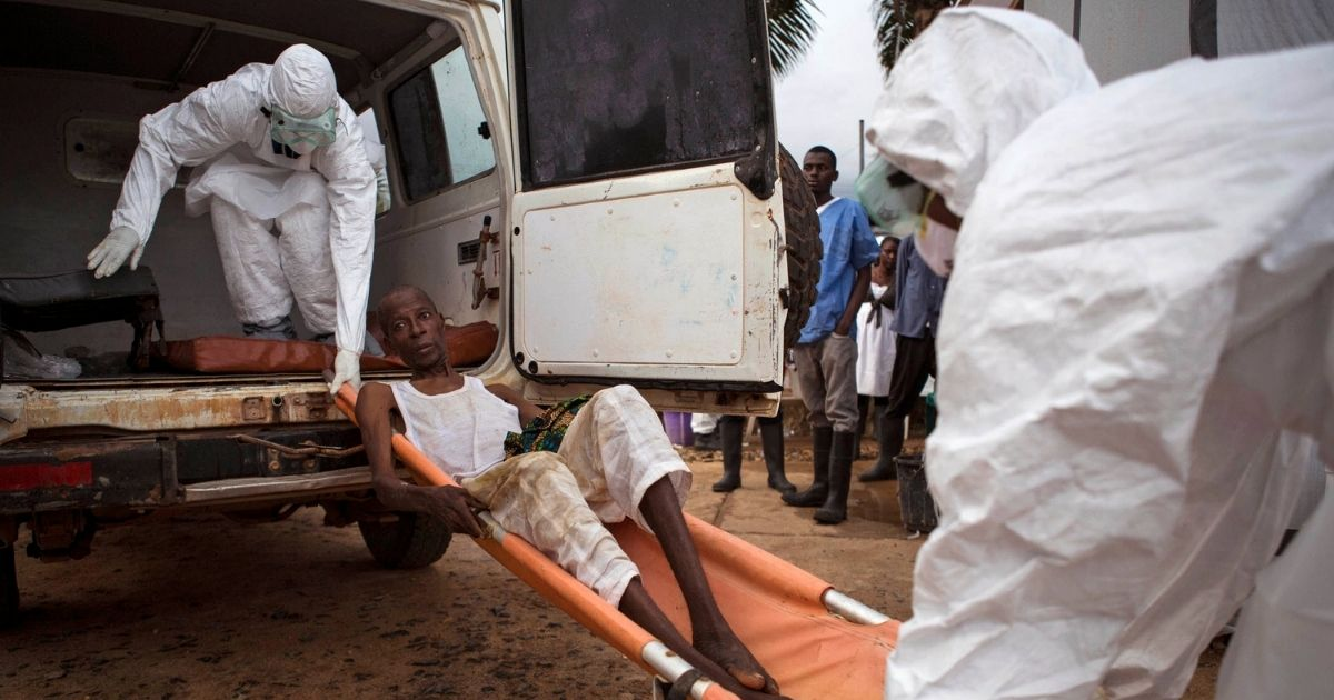 In this file photo taken on Wednesday, Sept. 24, 2014, health care workers load a man suspected of suffering from the Ebola virus onto an ambulance in Kenema, Sierra Leone.