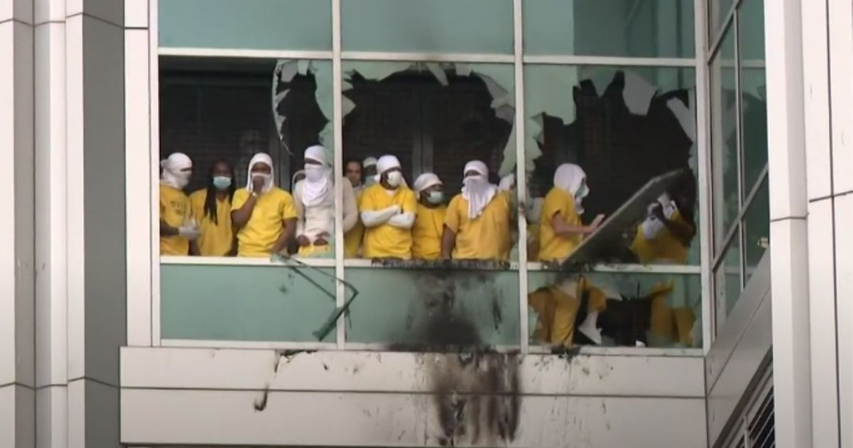 Inmates are shown throwing things out the broken windows during a riot in St. Louis City Justice Center on Saturday.