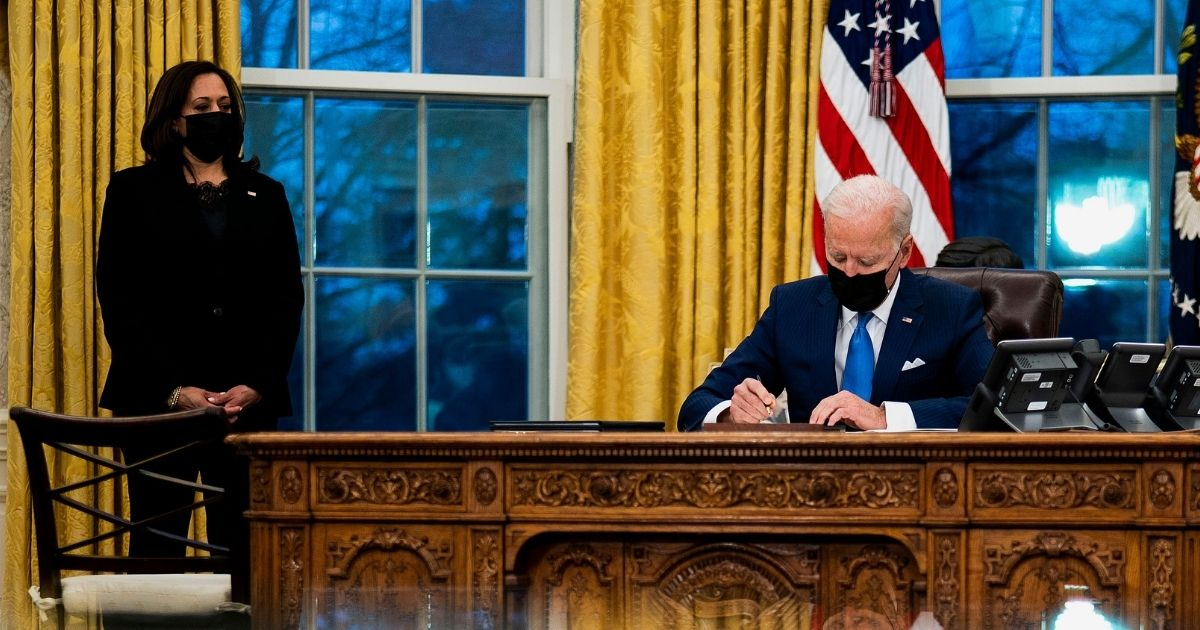 President Joe Biden signs several executive orders directing immigration actions for his administration as Vice President Kamala Harris looks on in the Oval Office at the White House on Feb. 2, 2021, in Washington, D.C.