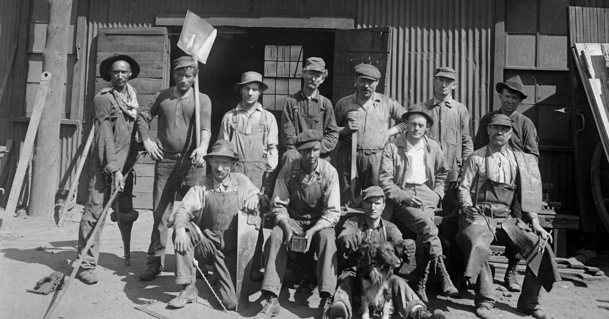 A group of tough looking laborers with their shovels, rakes, and implements, pose for a group portrait, circa 1920.