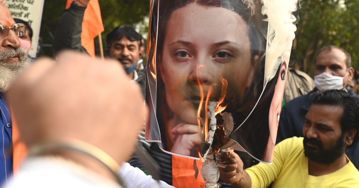 Activists of the United Hindu Front burn an effigy with a photo of Swedish climate activist Greta Thunberg during a demonstration in New Delhi on Thursday after she made comments on social media about ongoing mass farmers' protests in India.
