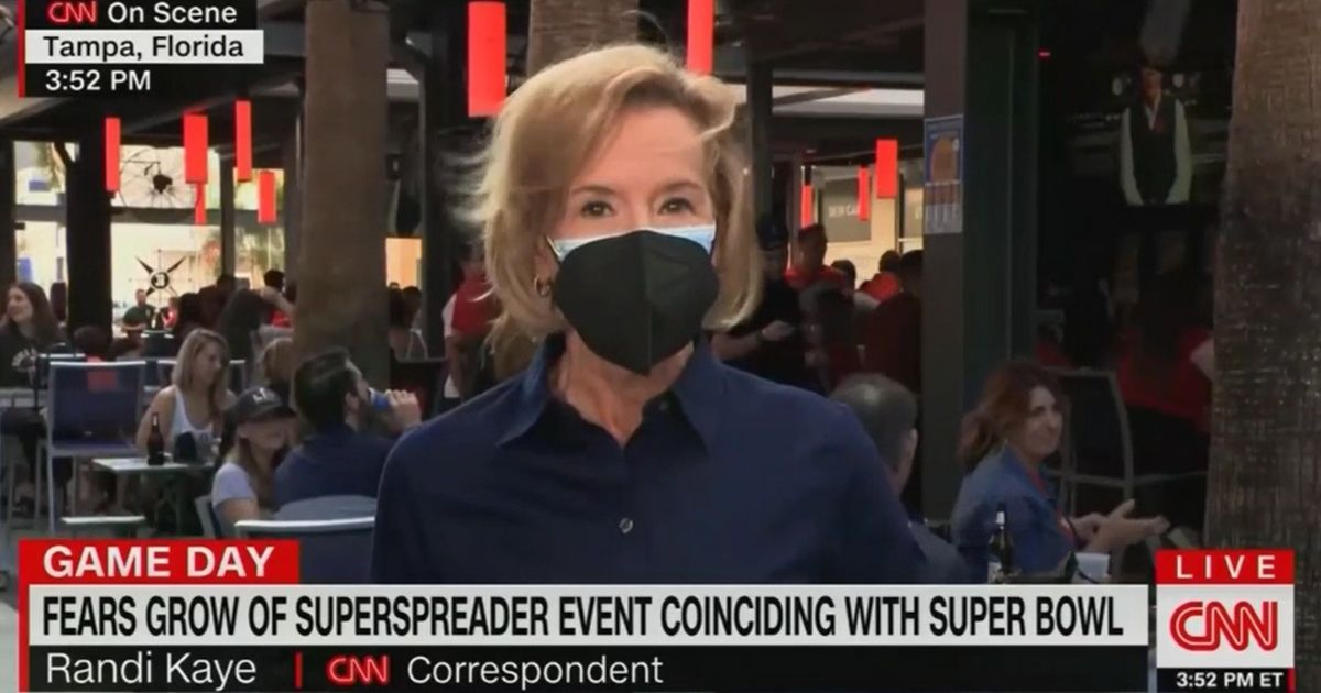 CNN's Randi Kaye wears two masks as she reports on Super Bowl visitors not wearing masks in Tampa, Florida.