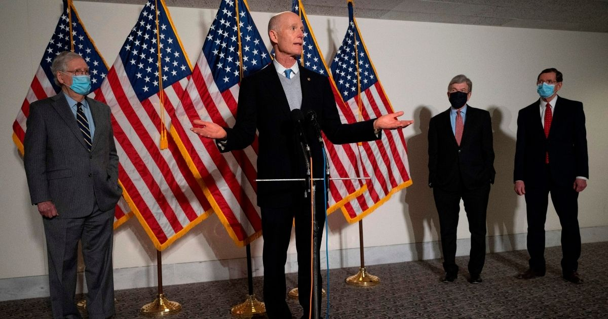 Florida GOP Sen. Rick Scott, center, speaks with Senate Minority Leader Mitch McConnell, left, Missouri GOP Sen. Roy Blunt, second from right, and Wyoming Republican Sen. John Barrasso after the Republican Policy Luncheon on Capitol Hill in Washington, D.C, on Jan. 26, 2021.