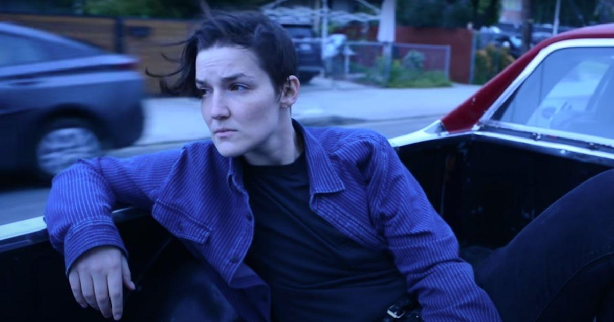 Grace Baldridge sits in the back of a pickup truck