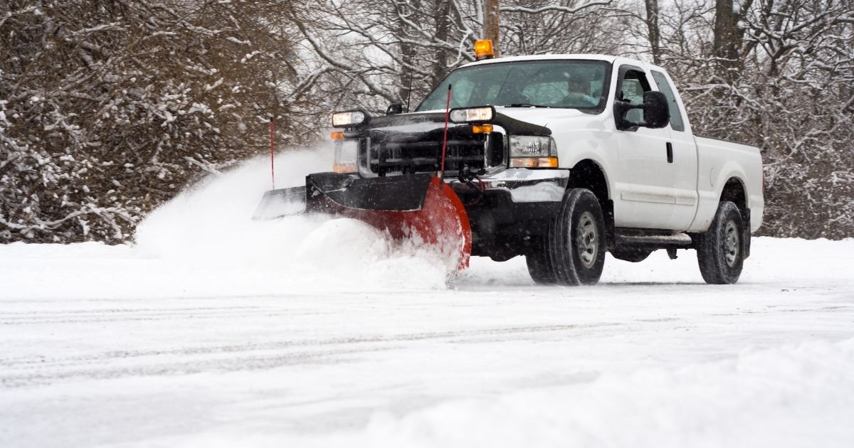 A man in a pickup truck plows snow in the stock photo above.