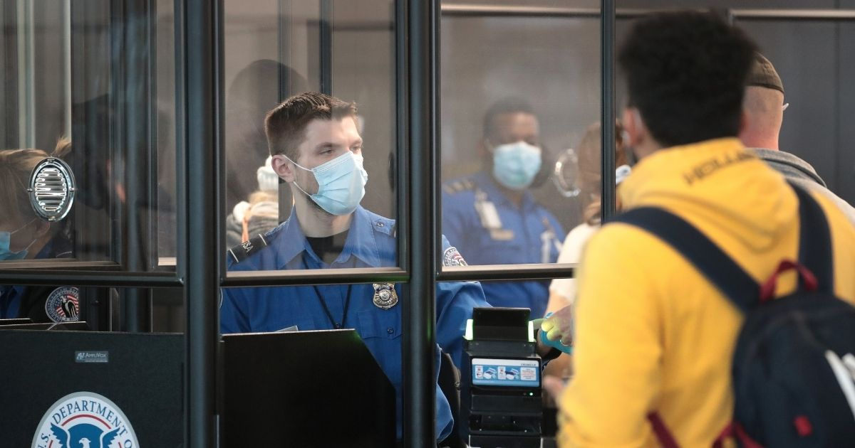 A Transportation Security Administration (TSA) agent screens an airline passenger at O'Hare International Airport on Oct. 19, 2020, in Chicago, Illinois.
