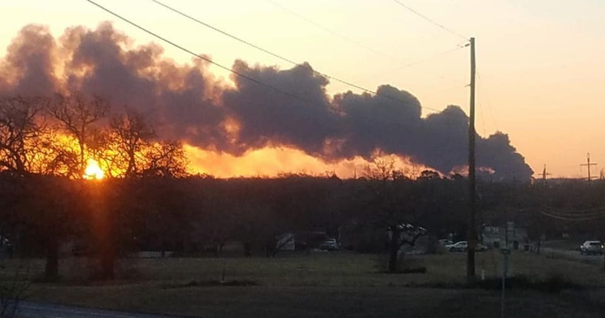 Smoke billows from a fire that began after a tractor-trailer and a train carrying petroleum collided near Cameron, Texas, on Tuesday.