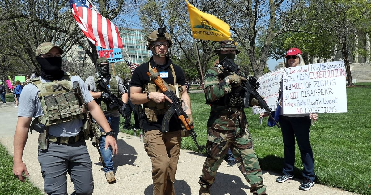 Armed veterans demonstrate in front of the state capitol building in Topeka, Kansas, on April 23, 2020, demanding that businesses be allowed to open, people be allowed to work, and lives be permitted to return to normal. The protest was part of a national movement against stay-at-home orders designed to slow the spread of the coronavirus.