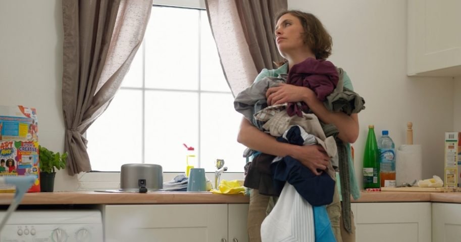 In this stock photo, a woman carries laundry in her home. In a China divorce court, a man was ordered to pay his ex-wife $7,700 for housework she did while they were married.