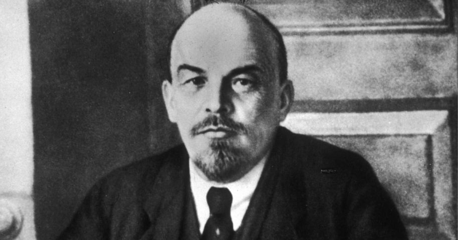 Pictured above is a portrait of Russian revolutionary leader Vladimir Lenin (1870 - 1924) sitting at a table during a meeting of the Sovnarkom.