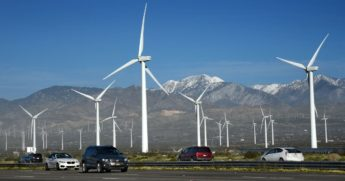 Automobiles travel along Interstate 10 as wind turbines generate electricity at the San Gorgonio Pass Wind Farm near Palm Springs, California.