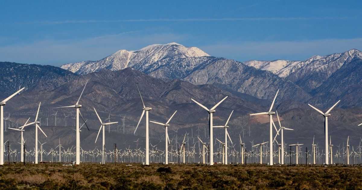 Wind turbines generate electricity at the San Gorgonio Pass Wind Farm near Palm Springs, California, with snow-covered Mt. San Jacinto in the background.