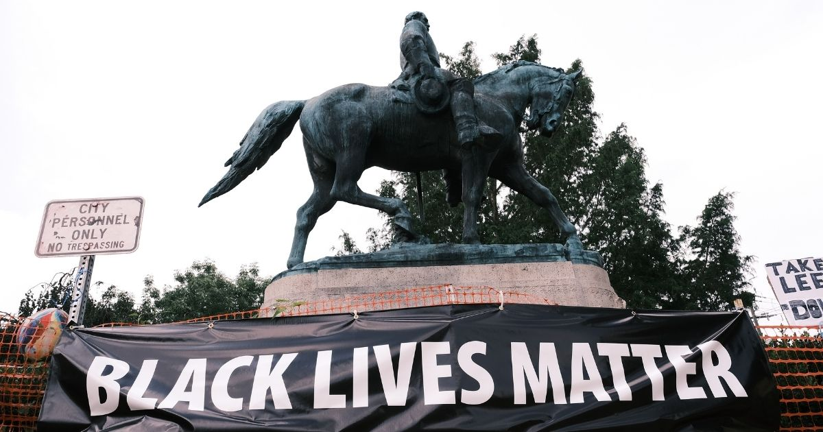 """A statue of Robert E Lee with a banner that reads """"Black Lives Matter"""" is seen on Aug. 12, 2020, in Charlottesville, Virginia."""