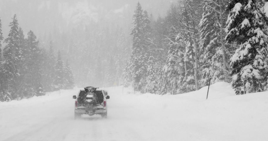 A pickup truck drives in the snow in the above stock image.