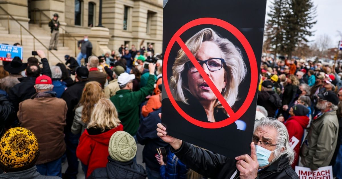 A man holds up a sign during a rally against Rep. Liz Cheney on Jan. 28, 2021, in Cheyenne, Wyoming.