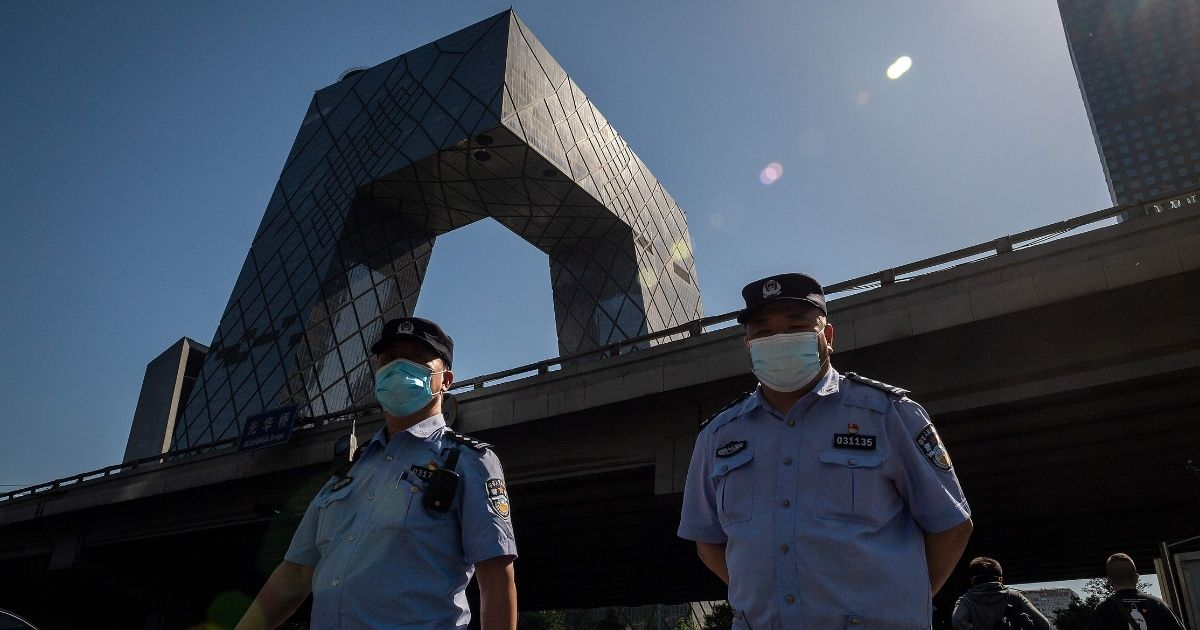 Police officers stand in front of the China Central Television headquarters building in Beijing on May 19, 2020.