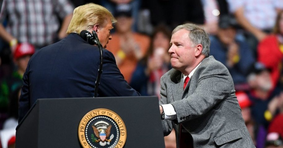 US Rep. Doug Lamborn shakes hands with President Donald Trump on stage during a rally on Feb. 20, 2020, in Colorado Springs, Colorado.