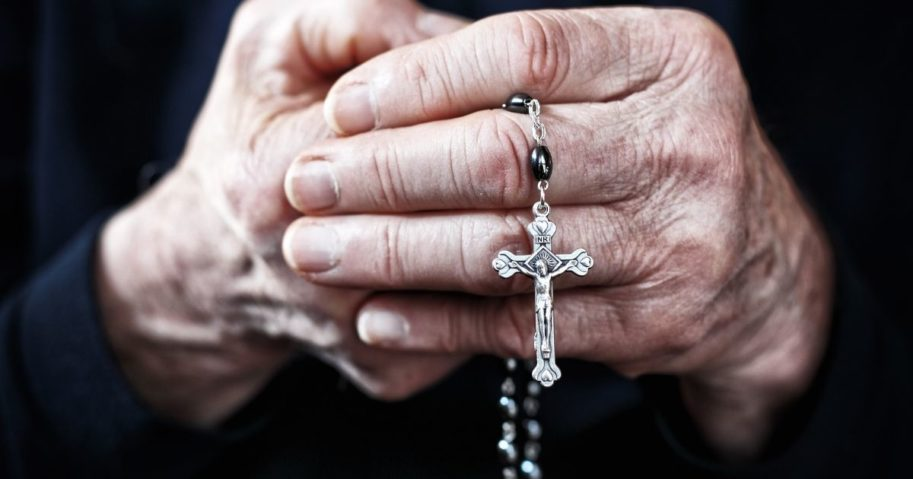 A nun prays a rosary in the above stock image.