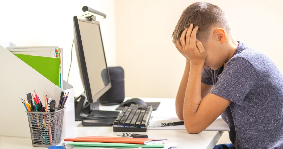 A boy sits in front of a computer in the above stock image.